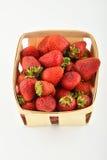 Mogna jordgubbar i träkorgen som isoleras på vit Royaltyfri Bild