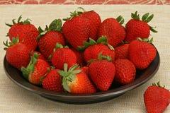 Mogna jordgubbar på en platta Arkivfoto
