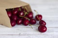 Mogna körsbär i en papperskraft packe på vita träkörsbär för en backgroundRipe i ett papper kraft packar på en vit träbakgrund, arkivfoto