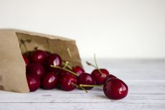Mogna körsbär i en papperskraft packe på vita träkörsbär för en backgroundRipe i ett papper kraft packar på en vit träbakgrund royaltyfria foton