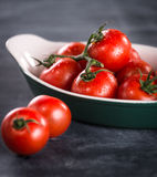 Mogna körsbärsröda tomater i en bunke på en svart bakgrund Royaltyfria Foton