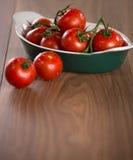 Mogna körsbärsröda tomater i en bunke på en trätabell Arkivfoto