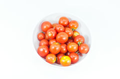 Mogna körsbärsröda tomater i en bunke på vit Royaltyfri Bild