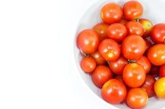 Mogna körsbärsröda tomater i en bunke på vit Arkivfoto