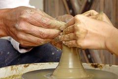 Mogna keramikerhänder som vägleder händerna av den unga kvinnan Fotografering för Bildbyråer