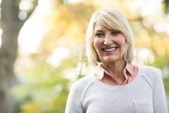 Mogna kvinnan som ler, medan stå i skog arkivbilder