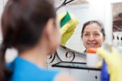 Mogna kvinnan som rengöringar avspeglar med snyltar Royaltyfri Foto