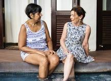 Mogna kvinnliga vänner på en semesterort arkivfoton