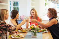 Mogna kvinnliga vänner som sitter runt om tabellen på matställepartiet Royaltyfri Bild