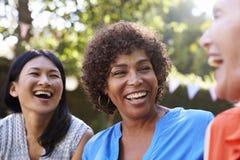 Mogna kvinnliga vänner som tillsammans umgås i trädgård royaltyfri bild