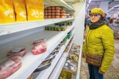 Mogna kvinnor som står i ett lager vid hyllorna med på burk gods arkivfoto