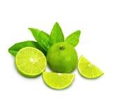 Mogna limefrukter med det gröna bladet bakgrund isolerad white Arkivbild