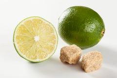 Mogna limefrukter och stycken av rått rottingsocker Arkivfoton