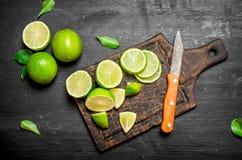 Mogna limefrukter på en skärbräda med en kniv Royaltyfria Foton