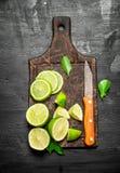 Mogna limefrukter på en skärbräda med en kniv Arkivfoto
