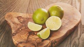 Mogna limefrukter på olivgrönt bräde Fotografering för Bildbyråer