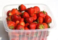 Mogna ljusa röda mogna jordgubbar i en plast- packe Arkivfoto