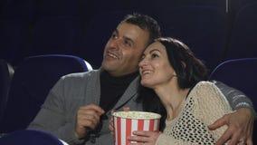 Mogna lyckliga par som tycker om deras datum på bion som håller ögonen på en film fotografering för bildbyråer