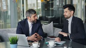 Mogna manaffärspartners som förhandlar avtalet som talar genom att använda bärbara datorn i kafé arkivfilmer