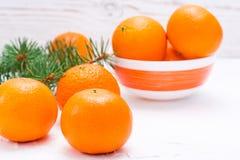 Mogna mandariner på en tabell och i en bunke och granfilialer Royaltyfri Fotografi