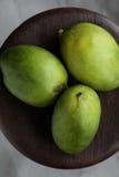Mogna mango på trätabellen Arkivfoton