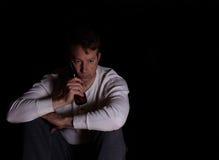 Mogna mannen i tanke, medan dricka öl i mörk bakgrund Fotografering för Bildbyråer