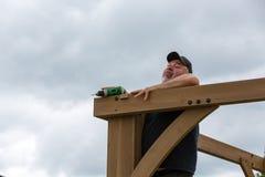 Mogna mannen som faller, medan bygga träpergolan arkivbild