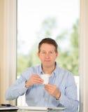Mogna mannen som tycker om kaffe medan på arbete Arkivbilder