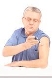 Mogna mansammanträde, och injicera insulin i hans beväpna Royaltyfri Bild