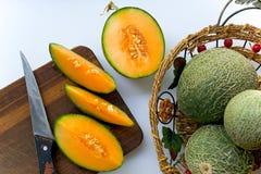 Mogna melon, guling inom med en grön skorpa är hela och snittet som ligger i en korg och på tabellen Arkivbild