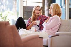 Mogna modern med den vuxna dottern som kopplar av på Sofa At Home fotografering för bildbyråer
