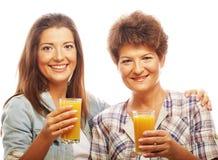 Mogna modern och yungdottern med fruktsaft Fotografering för Bildbyråer