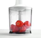 Mogna, mogna och söta jordgubbar är i en blandare på en grå tabell som isoleras på en vit bakgrund Arkivfoto