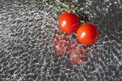 Mogna nya Cherry Tomatoes på brutet spegelexponeringsglas arkivfoton