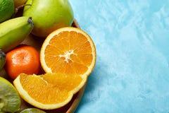 Mogna nya frukter i en träplatta på en blå bakgrund, selektiv fokus, närbild, bästa sikt arkivbilder