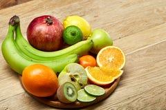 Mogna nya frukter i en träplatta på en ljus träbakgrund, selektiv fokus, närbild, bästa sikt arkivfoto