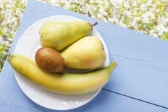 Mogna nya frukter på träblåtttabellen och på naturlig bakgrund för vita blommor Banan, kiwi och päron för vegetarisk breakfa Arkivfoto