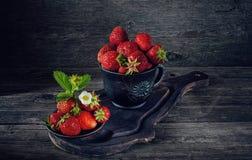 Mogna nya jordgubbar i en lerakruka i en lantlig stil konst royaltyfri bild