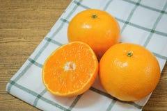 Mogna och söta apelsiner på en trätabell Arkivfoto