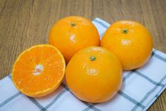 Mogna och söta apelsiner på en trätabell Fotografering för Bildbyråer