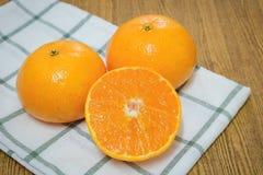 Mogna och söta apelsiner på en trätabell Royaltyfri Bild