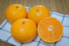 Mogna och söta apelsiner på en trätabell Royaltyfria Bilder