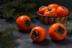 Mogna orange persimonfrukter är på tabellen och i en vide- korg royaltyfri fotografi