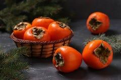 Mogna orange persimonfrukter är på tabellen och i en vide- korg royaltyfria bilder