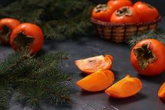 Mogna orange persimonfrukter är på tabellen och i en vide- korg arkivfoto