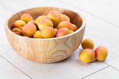 Mogna organiska aprikosfrukter i träbunke för askaträd fotografering för bildbyråer