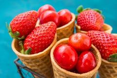 Mogna organiska jordgubbar, glansiga söta körsbär i dillandeglasskottar i trådkorgen, blå bakgrund, utformad bild Royaltyfri Bild