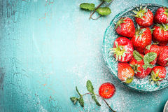 Mogna organiska jordgubbar med mintkaramellsidor i turkos bowlar på blå träbakgrund, bästa sikt royaltyfria bilder