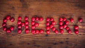 Mogna organiska självodlade körsbär, körsbärsröd text Arkivfoto