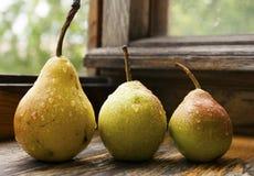 Mogna päron på en trätabell med vatten tappar Arkivbilder